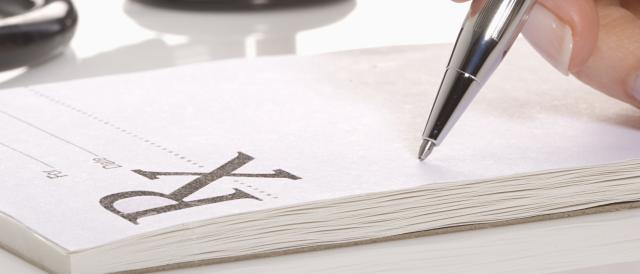 Close up of a hand using a pen to write out a prescription on a pad of paper