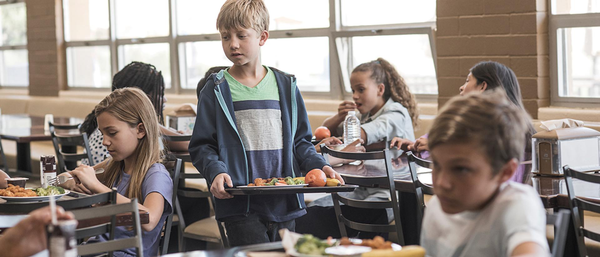 Child holding a lunch tray of food in a school cafeteria
