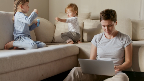 A woman is on laptop with two children blowing bubbles on couch next to her.
