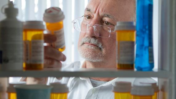 Pharmacist looking at bottles of prescription pills