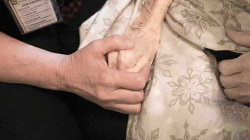 Blue Shield California palliative care worker holding the hand of a patient with cancer