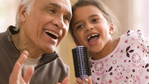 older man and little girl singing into a microphone