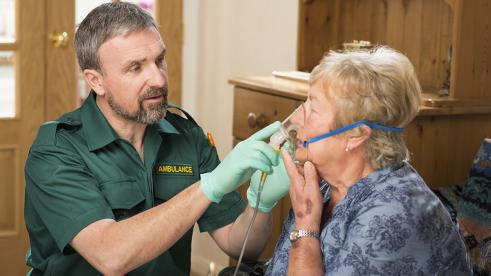 paramedic treating woman at her home