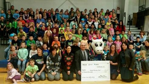 Gentleman presenting large check to group of kids and community