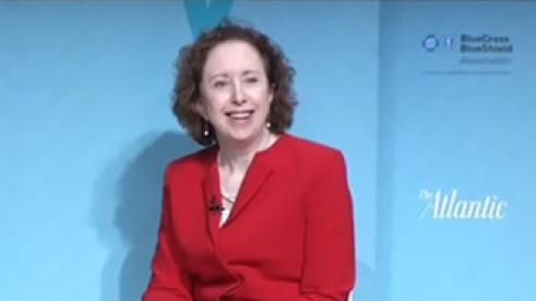 Maureen Sullivan sitting in front of blue background