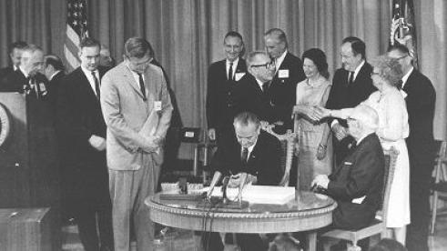 Lyndon B. Johnson signing Medicare into law