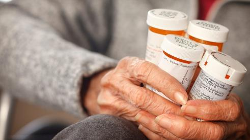 Senior citizen holding bottles of prescription medications