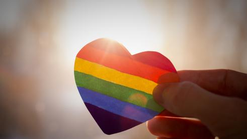 hand holding rainbow colored heart