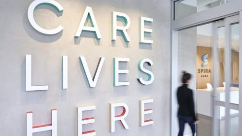 "Interior of Spira Care center; wall reads ""Care Lives Here"""