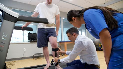 A man on a treadmill having his leg brace examined by two professionals