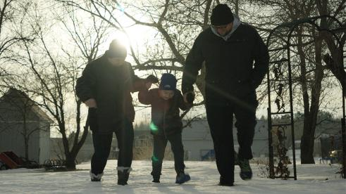 A mother and father walking with their child in a forested area in winter