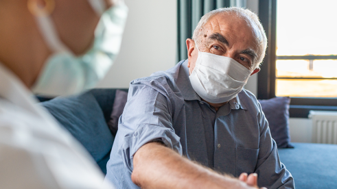 Senior wearing mask with a Doctor