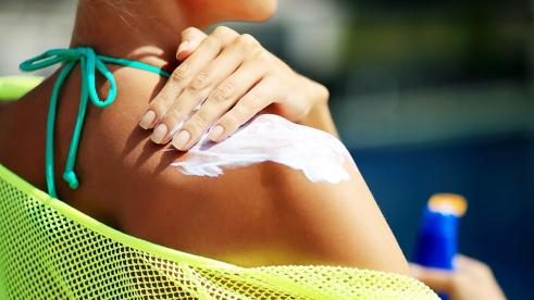 lady applying sunscreen to shoulder