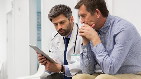 A doctor and patient reading colorectal cancer information