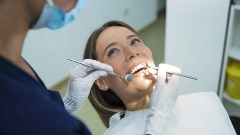 Woman getting her teeth cleaned at the dentist's office