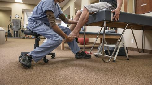 Doctor administering physical therapy on a patient's knee