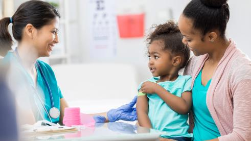 Doctor giving a vaccination to a child being held by her mother