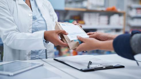 Pharmacist handing a bag to a customer