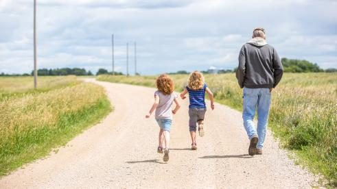 A father and his children walking on a road in rural Nebraska