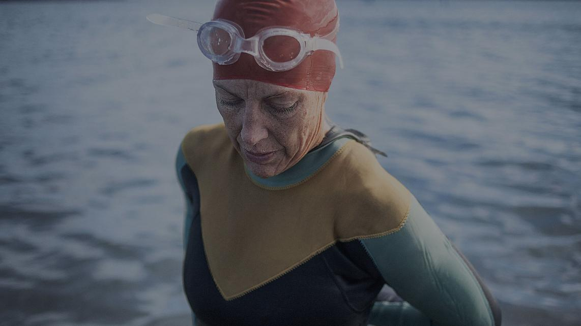 A woman is ready to start swimming in the lake