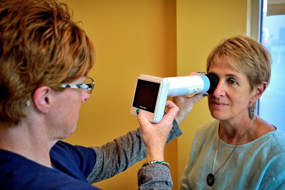 Staff at St. Joseph's Primary Care Center West in Syracuse demonstrate how easy the new dilated retinal eye exam equipment is to use in the primary care setting.