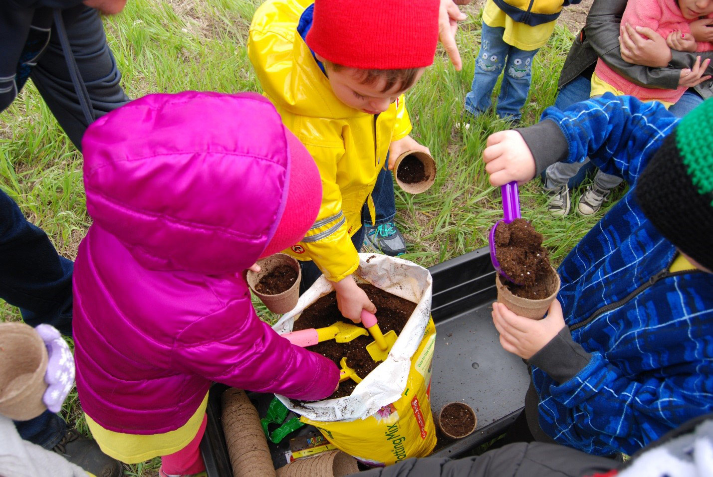 Children digging soil out of a pot for planting flowers
